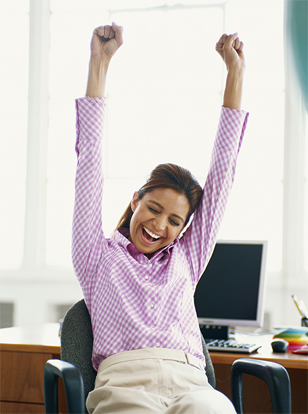 Businesswoman sitting in office with raised hands