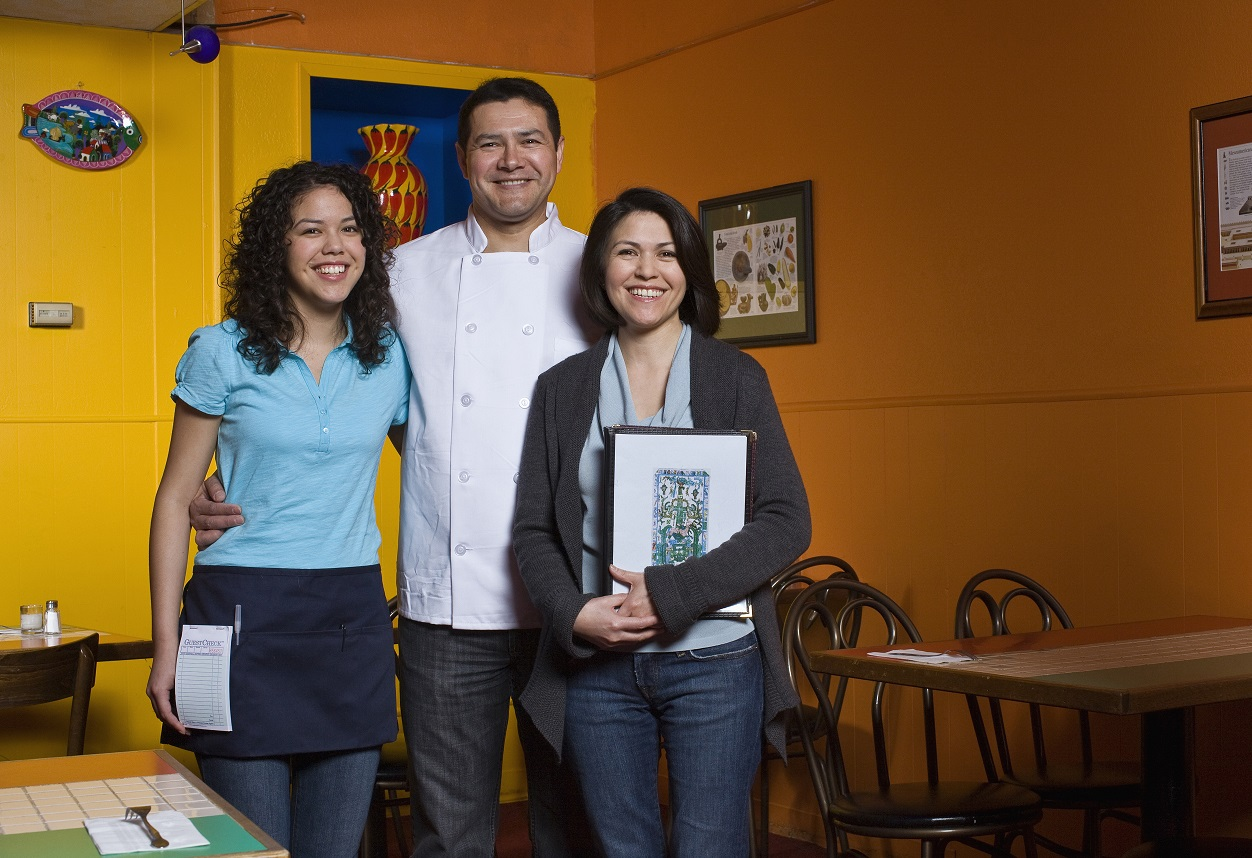 family portrait of small business owners. mexican restaurant owners