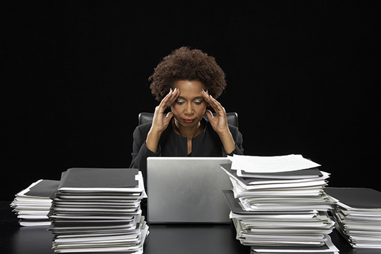Businesswoman using laptop surrounded by files, with hands to head